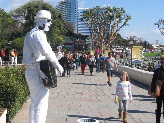 Birds perch on guitar-playing white statue-man.