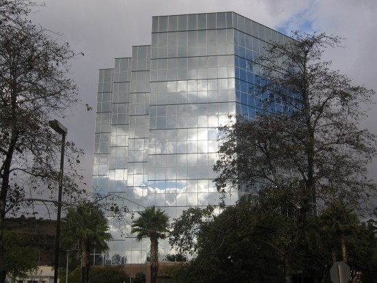 Blue patch reflected in a building beneath clouds.