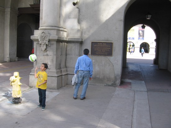 Boy plays with ball while man reads Balboa Park plaque.