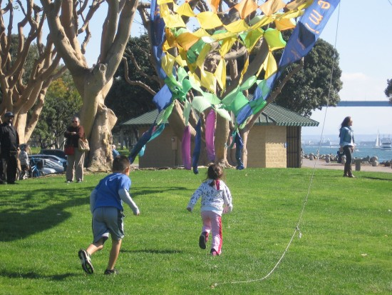 Children play beneath colorful kite near Seaport Village.