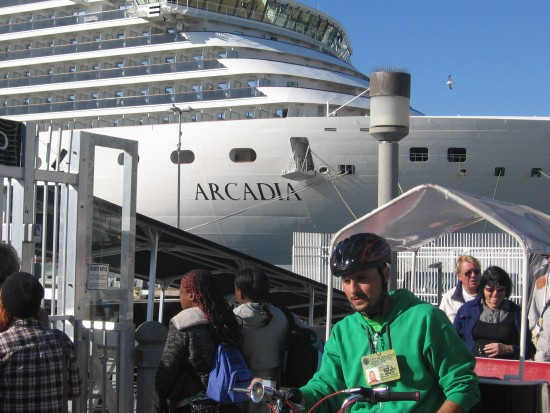 Cruise ship Arcadia rises beyond tourists and pedicab.