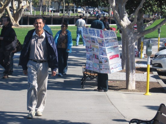 Falun Gong activist holds up sign on sidewalk.
