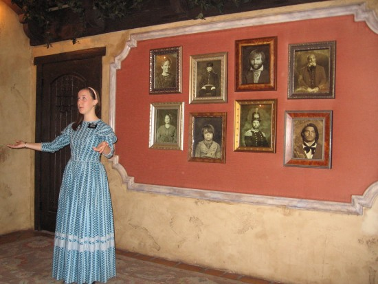 Girl in pioneer dress begins tour with talking, moving portraits.