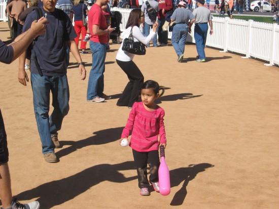 Small girl with a big pink baseball bat.