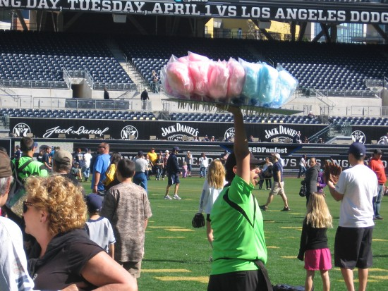 A vendor with cotton candy moves through the crowd on the field.