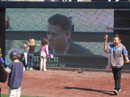 Kids check out the big display on the outfield wall.