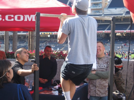 Padres fan does pull-ups at Marines booth at Fanfest.