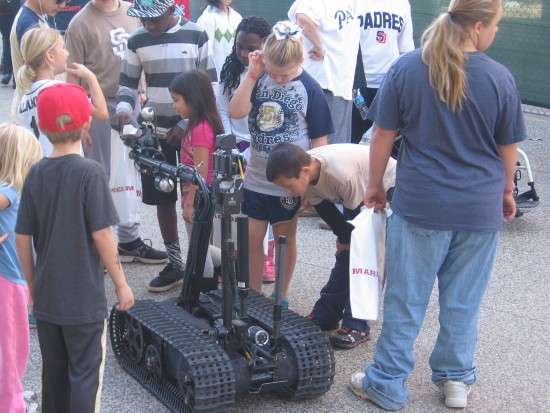 A military robot fascinates kids at Padres Fanfest.
