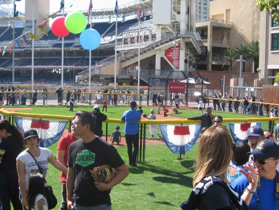 People watch kids playing baseball during Padres Fanfest.