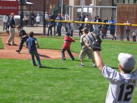 Kids play in the tiny baseball field at the Park at the Park.