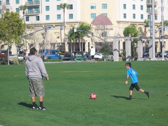 Kid kicks a ball on grass by Ruocco Park.