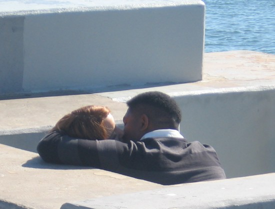 Lovers have an intimate moment by the water.