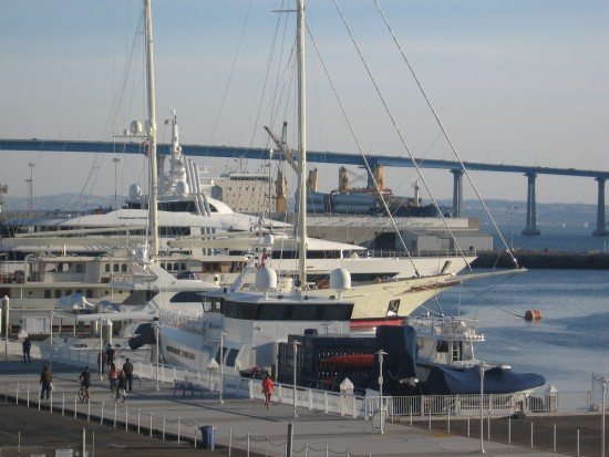 Luxury yachts with Coronado Bay Bridge in background.