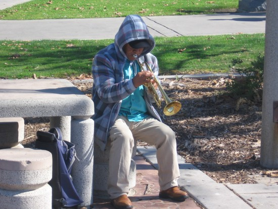 Man with horn plays Mariachi tunes near the USS Midway.