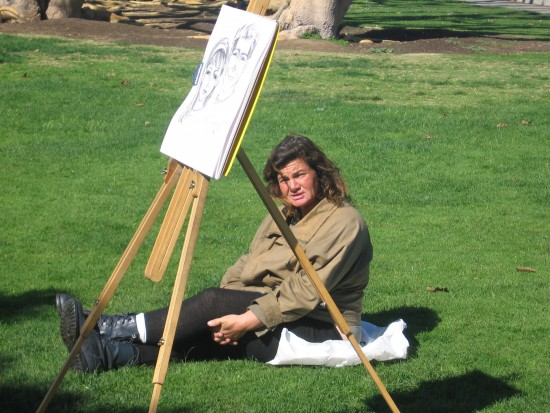 Resting on the grass, waiting to sketch a tourist portrait.
