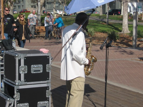 Sax player entertains people on San Diego waterfront.