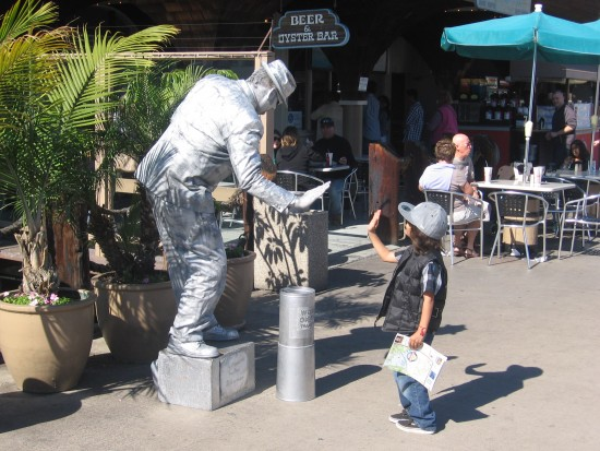 Silver robotic mime and a frozen high five.