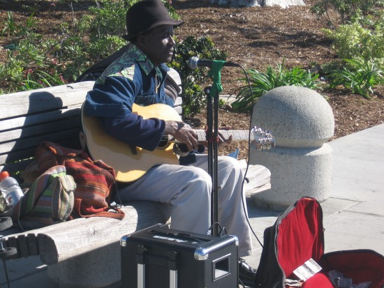 Street performer on a bench plays guitar and sings.