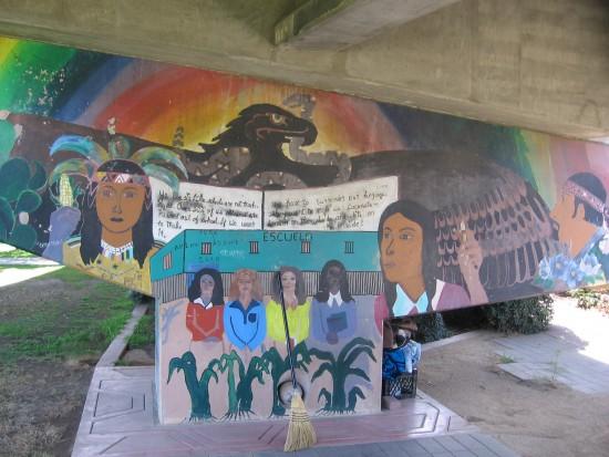 Broom leans up against mural of students in school.