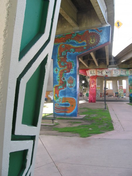 A series of murals on pillars supporting traffic lanes.