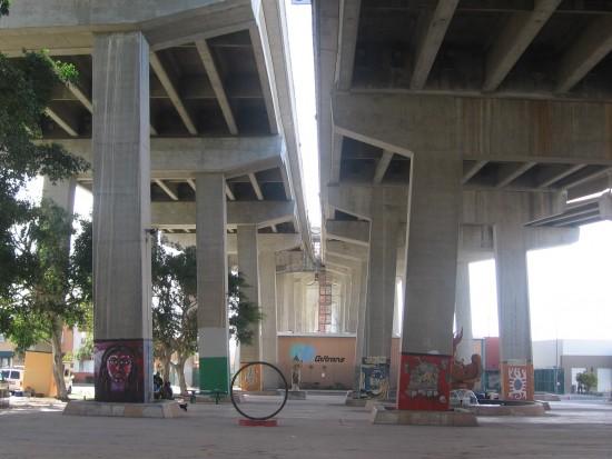 Wide view under Coronado Bay Bridge reveals murals and sculptures.
