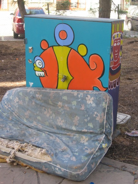 Mattress of homeless person leans up against painted utility box.