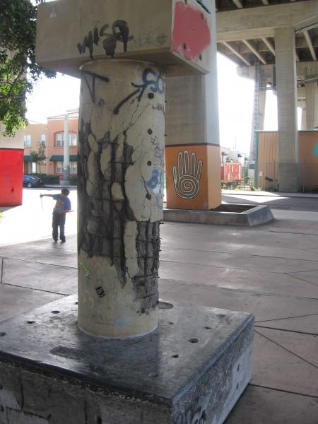 Kid plays among pillars under Coronado Bay Bridge.