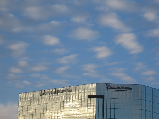 Gauzy clouds above a silver building.
