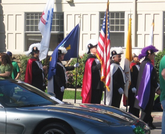 Gentlemen in capes and plumed hats hold flags.