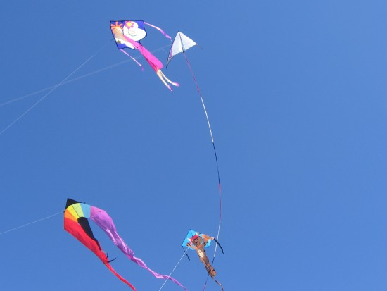 Four colorful kites in a clear blue sky.