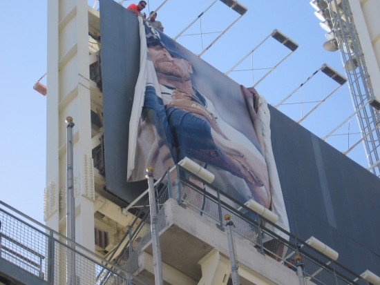 Two workers put up large Padres banner at Petco Park.