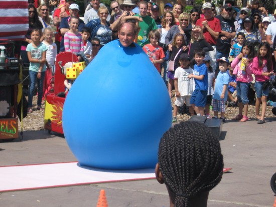 Skip Banks' head pops out of big balloon at Busker Festival.