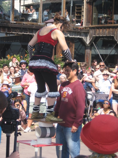 Acrobatic juggler entertains crowd with spectator's help.