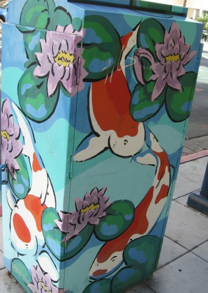 Koi and pond flowers adorn a colorful utility box.