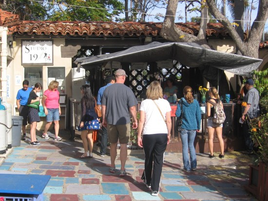 People converge to see glassblowing in progress.