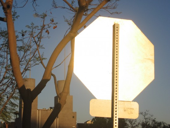 Back of stop sign flashes silver in the morning sunlight.