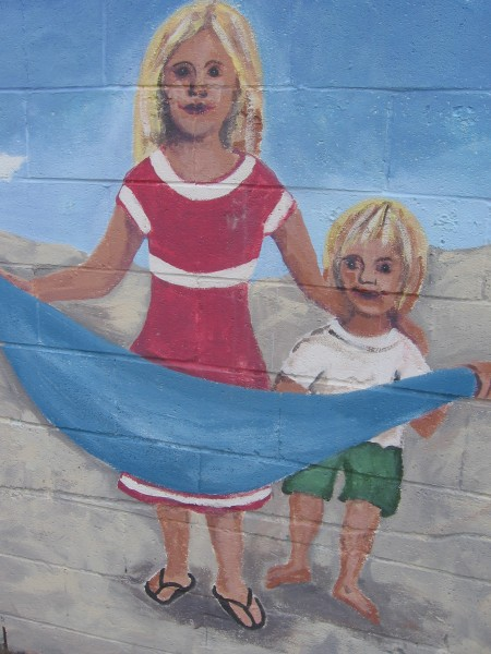 Happy faces at the beach on an outdoor mural.
