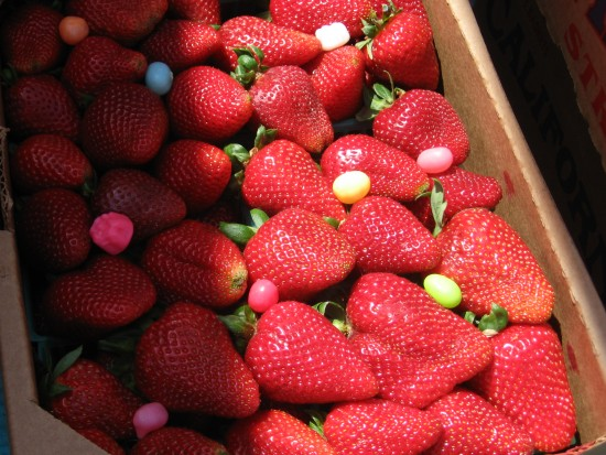 Ripe red strawberries mixed with Easter candies.