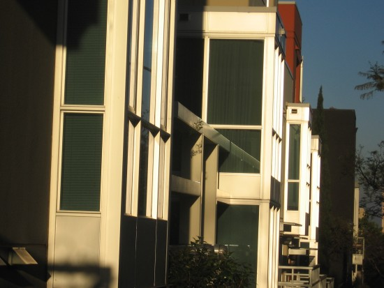 Slanting sunshine on building highlights layered geometry.