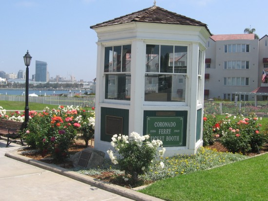 Old Coronado ferry ticket booth surrounded by flowers.