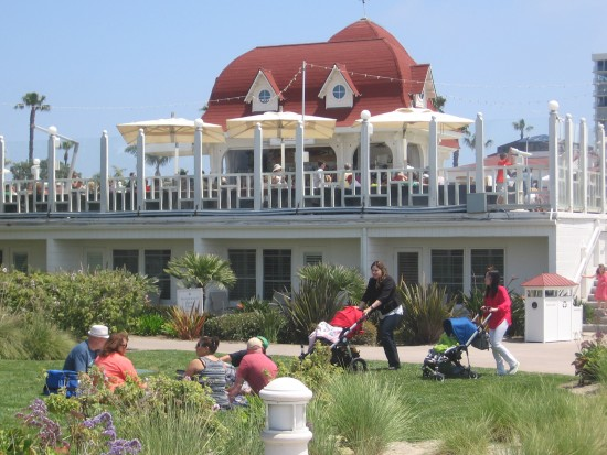 Pushing strollers past some outdoor dining.