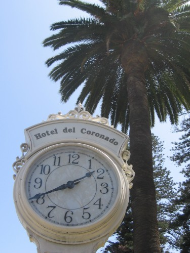 Clock stands on sidewalk among palm trees in front of hotel.