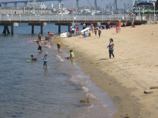 Kids play on the beach next to the ferry landing pier.