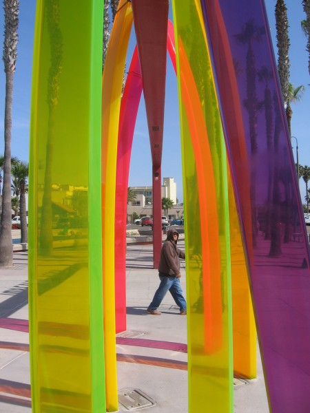 Colorful surfboard arches frame a pier visitor.