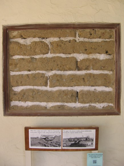 Gap in Lodge's stucco shows original adobe bricks.