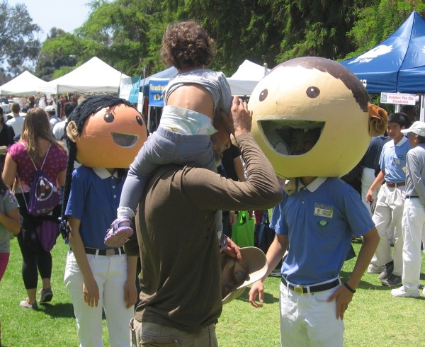 Costumed characters greet a child at EarthFair.