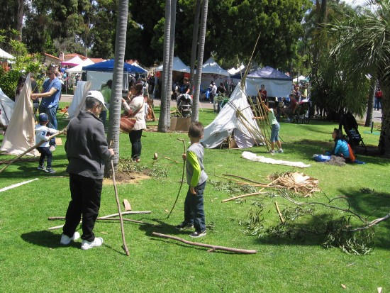 Kids learn how to set up teepees on a Balboa Park grassy area.