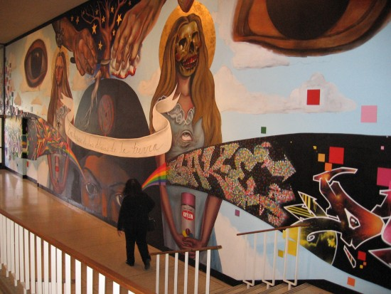 San Diego Museum of Art visitor walks past large indoor mural.