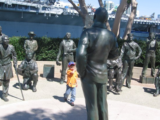 USS Midway can be seen behind the bronze service members.