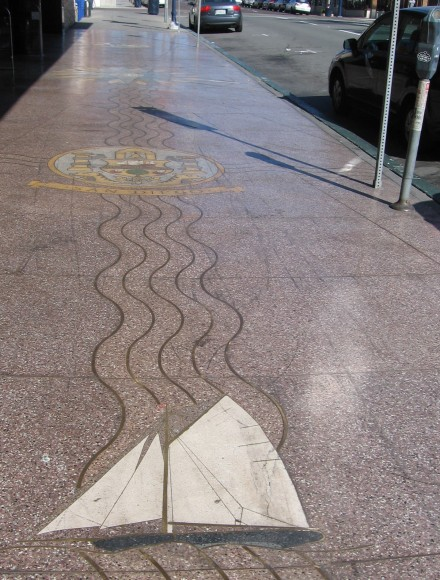 The empty sidewalk contains images tread by many feet.